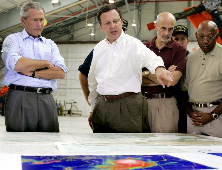 President George W. Bush (L) and Homeland Security Secretary Michael Chertoff (2nd R) get a briefing from Federal Emergency Management Agency (FEMA) chief Michael Brown (C) upon their arrival 02 September, 2005, at a US Coast Guard Base in Mobile, Alabama, before touring the devastation left by Hurricane Katrina. (Photo: Jim Watson/AFP/Getty Images)
