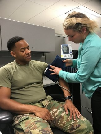 """Health Promotion Technician Meredith Putney administers a blood pressure check on Lt. Col. Devon """"Dru"""" Roberts"""