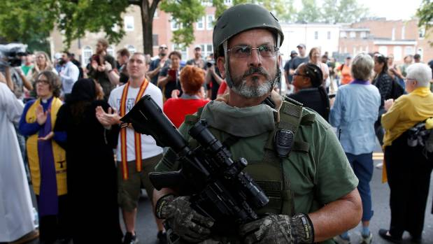 A white supremacist militia member stands in front of clergy counter protesting during rally in Charlottesville.