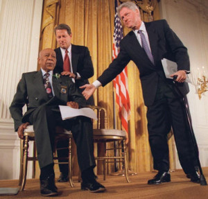 President Clinton and Vice President Al Gore, back, help Herman Shaw, 94, a Tuskegee Syphilis Study victim, during a news conference Friday, May 16, 1997. Making amends for a shameful U.S. experiment, Clinton apologized to Black men whose syphilis went untreated by government doctors. (AP Photo/Doug Mills)