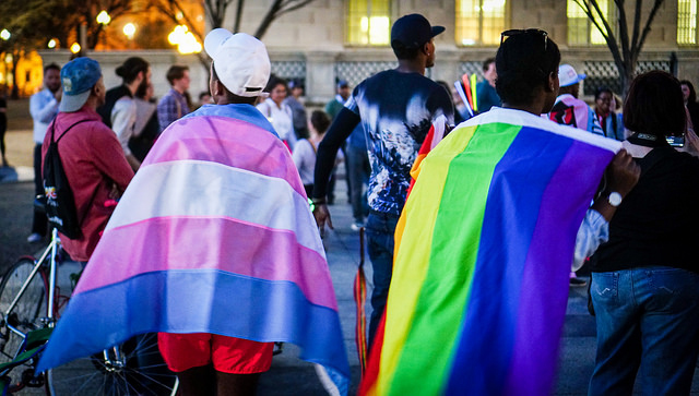 Protesters drape themselves in the LGBTQ+ pride flag and Trans pride flag at a dance protest celebrating trans youth in Washington, DC, February 24, 2017. (Photo: Ted Eytan)