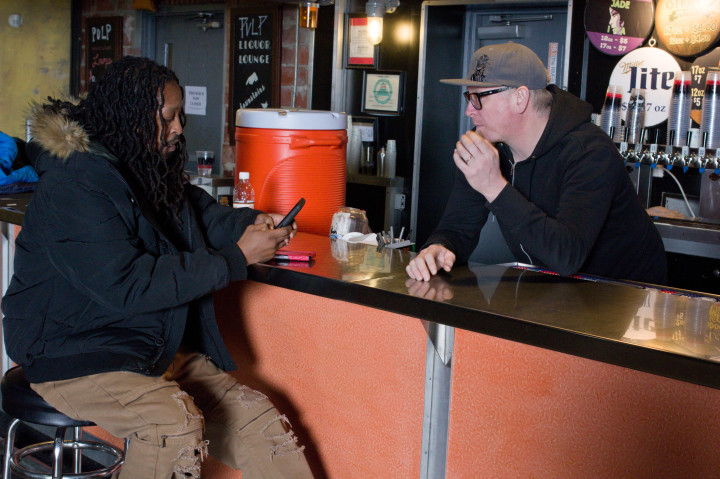 """BUSINESSMEN: Local music promoter Duke """"Party Man"""" Finley, left, and Justin Ferraby, operations manager at The Orange Peel, chat at the venue's bar. Ferraby says he welcomes emails and calls from local hip-hop artists and is willing to give them a chance. Photo by Cindy Kunst"""