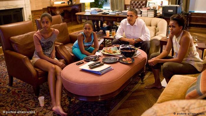 Obama family on couches and chairs, watching TV (picture-alliance/dpa)