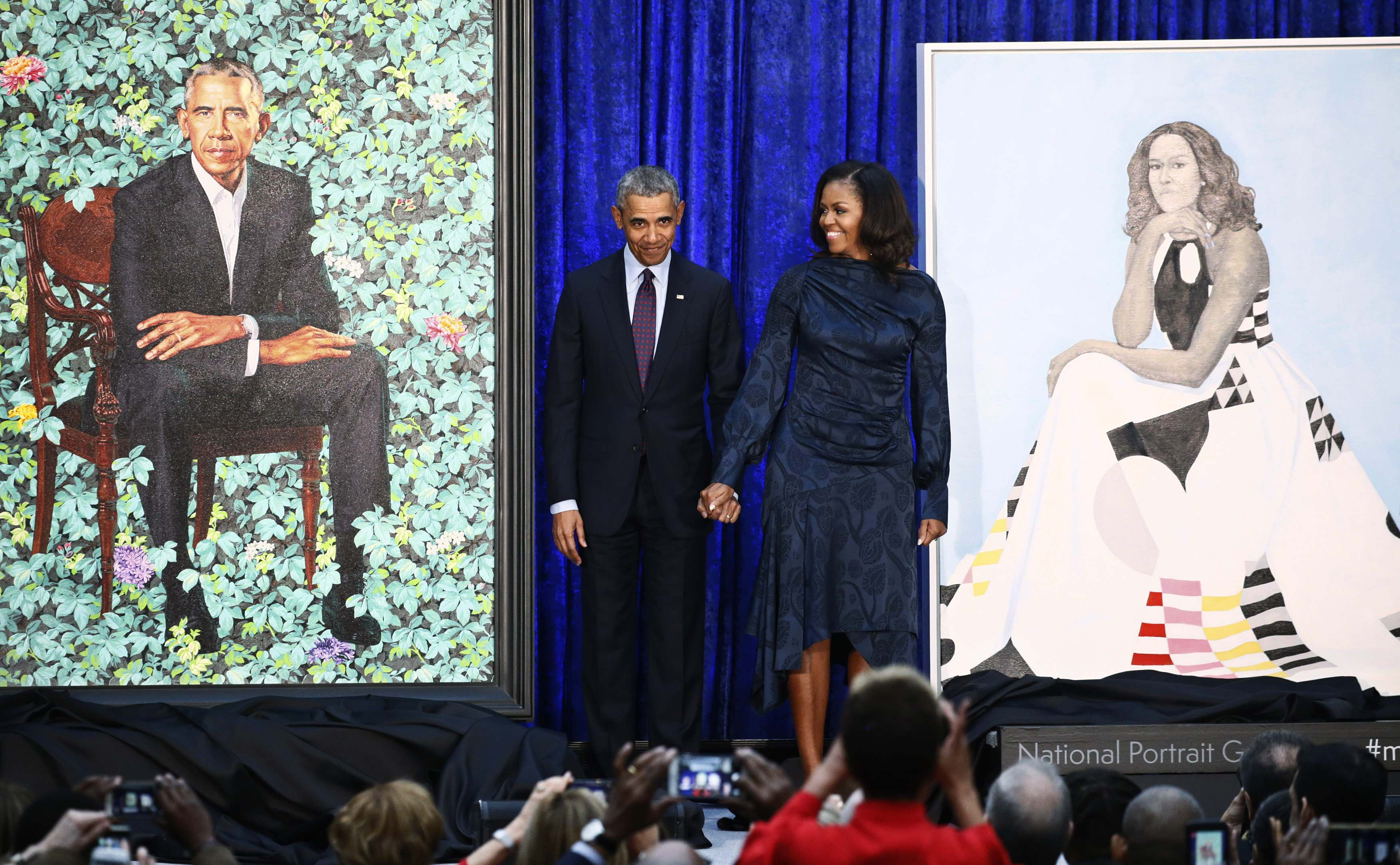 Former US President Barack Obama and former first lady Michelle Obama hold hands between their portraits during an unveiling ceremony at the Smithsonian's National Portrait Gallery in Washington, February 12, 2018. — Reuters pic