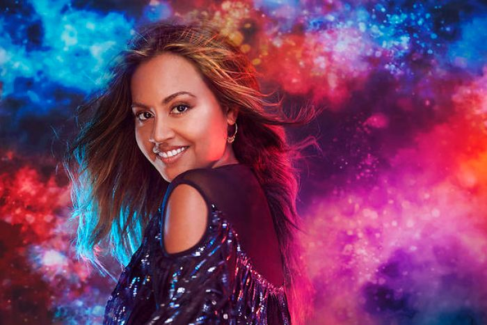 Jessica Mauboy promo picture facing camera. Pink, red, orange and red clouds in the background.