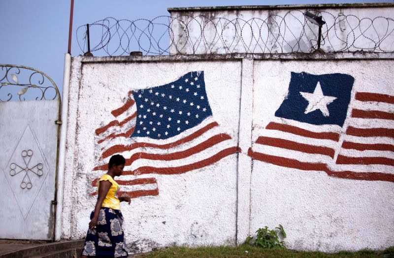 A woman in Monrovia walks past a mural of the Liberian and American flags. Liberia was formed by the American Colonization Society, an organization that resettled free African-Americans and freed slaves.