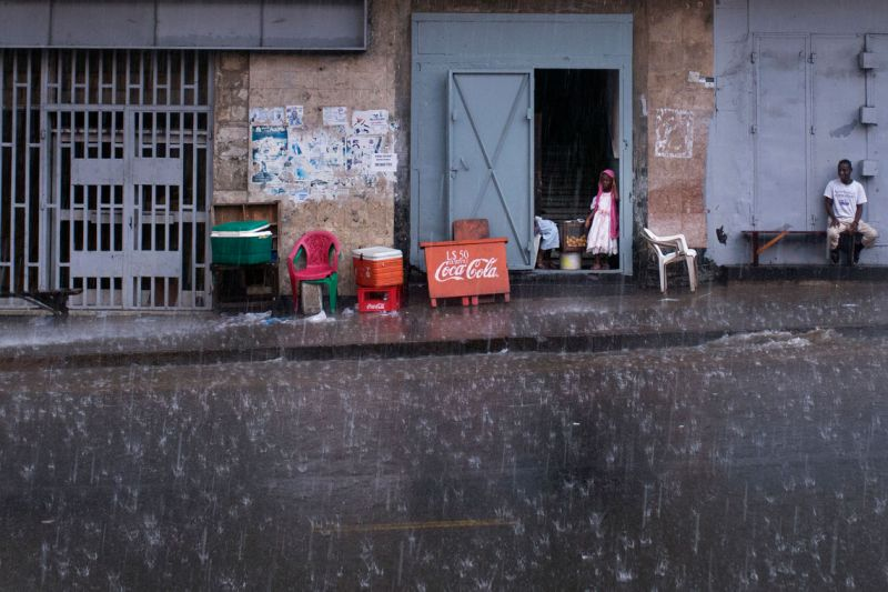 A little girls looks out onto Ashmun Street in Monrovia, Liberia. Rainy season lasts more than half the year in Liberia.