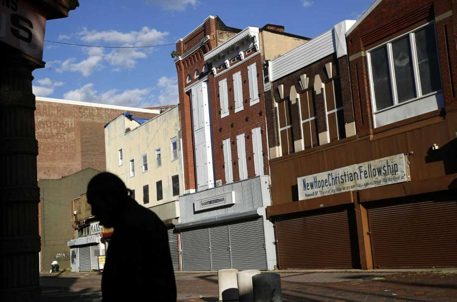 In this Tuesday, Oct. 17, 2018 photo, a man walks past vacant storefronts at the Old Town Mall in Baltimore. Job growth was supposed to be a cure-all to stop the wealth gap from worsening, but new research suggests that impoverished Americans are getting left out even when their communities enjoy hiring booms. (AP Photo/Patrick Semansky) Photo: Patrick Semansky / Copyright 2018 The Associated Press. All rights reserved.