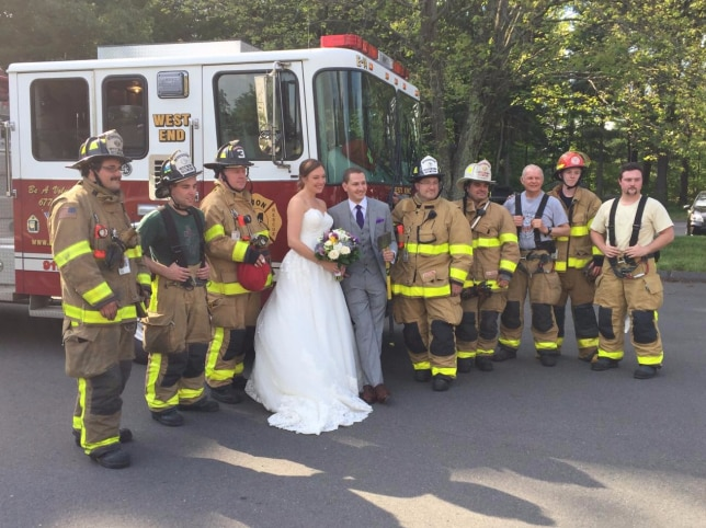 Maria Leonardi and Justin Stone pose with the firefighters who gave them a lift to their reception after their bus caught fire.