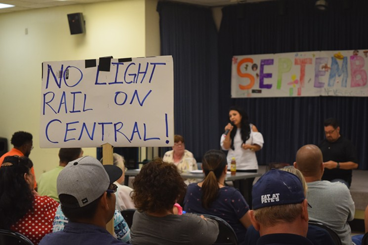 Eduardo Sanchez, 24, holds a sign at a community meeting on light rail on September 17. In the background, from left, are City Council members Debra Stark, Felicita Mendoza, and Michael Nowakowski.