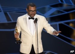 "FILE - Jordan Peele accepts the award for best original screenplay for ""Get Out"" at the Oscars at the Dolby Theatre in Los Angeles, March 4, 2018."