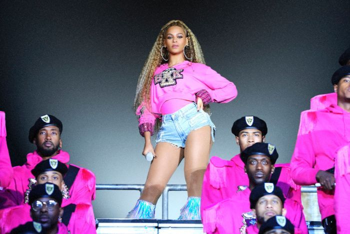 Beyonce stands at the top of a platform surrounded by male dancers in pink suits in a still from her Netflix documentary.