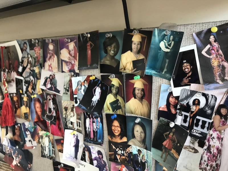 Dozens of school photos and prom pictures are tacked haphazardly to a bulletin board