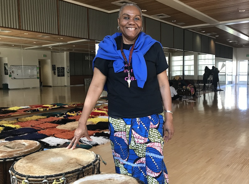 Subject of profile -- Naomi Diouf, 64 year old black woman wearing a t-shirt and African print skirt -- stands with her hand on a bongo drum. Dance studio is visible behind her.