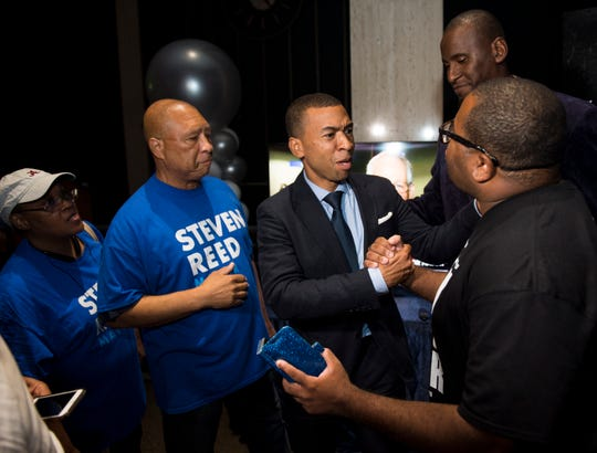 Mayoral candidate Steven Reed shakes hands with family and supporters at his campaign headquarters in Montgomery, Ala., on Tuesday, Aug. 27, 2019. Reed will face off with David Woods in an Oct. 8 runoff election.