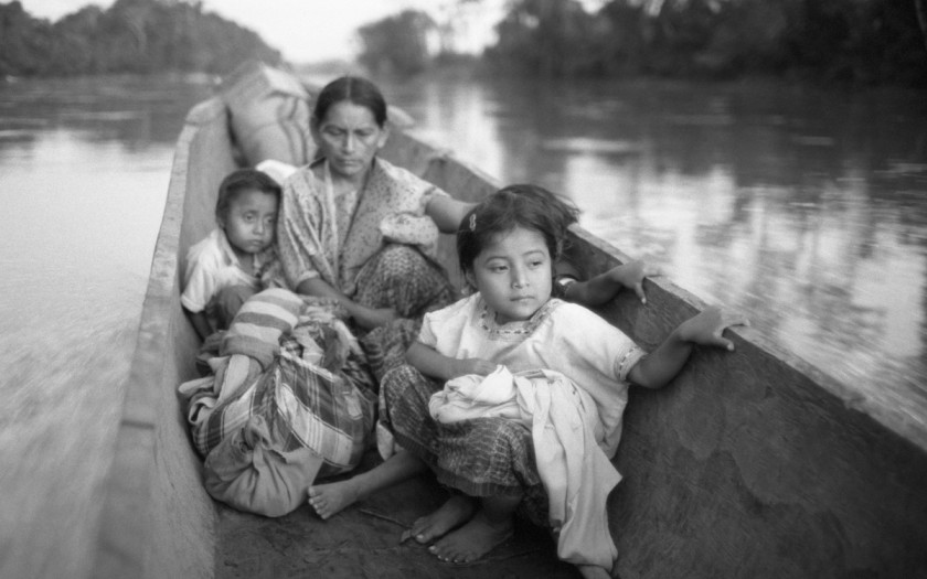 """""""Refugee woman and three children in a canoe, Chiapas,"""" 1983, by Richard Cross, on view at L.A.'s Museum of Social Justice."""