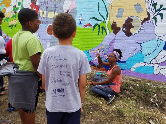 """Tia Richardson coaches volunteers on how to paint details of the """"Sherman Park Rising"""" mural, a reaction to a disturbance in the summer of 2016 in the neighborhood. The City of Milwaukee Arts Board named Richardson one of its 2018 Artists of the Year."""