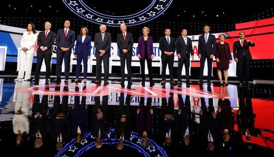 From left, Democratic presidential candidates, Rep. Tulsi Gabbard, D-Hawaii, businessman Tom Steyer, Sen. Cory Booker, D-N.J., Sen. Kamala Harris, D-Calif., Sen. Bernie Sanders, I-Vt., former Vice President Joe Biden, Sen. Elizabeth Warren, D-Mass., South Bend Mayor Pete Buttigieg, entrepreneur Andrew Yang, former Texas Rep. Beto O'Rourke, Sen. Amy Klobuchar, D-Minn., and former Housing Secretary Julian Castro stand on stage for a photo before a Democratic presidential primary debate hosted by CNN and The New York Times at Otterbein University, Tuesday, Oct. 15, 2019, in Westerville, Ohio. (AP Photo/Tony Dejak) ORG XMIT: NYAG202