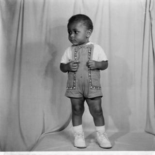 A toddler wearing a T-shirt, dungarees and lace-up shoes poses inside the camera studio.