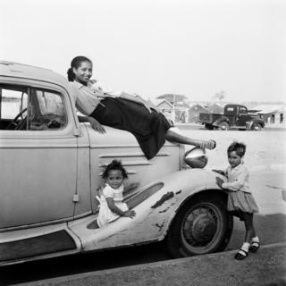 A woman, Madame Gomez, poses on top of car with two young children stood by the vehicle.