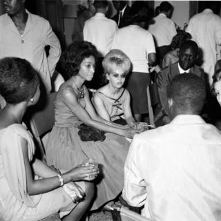 Men and women dressed in eveningwear are seen sitting down and talking with drinks and cigarettes in hand.