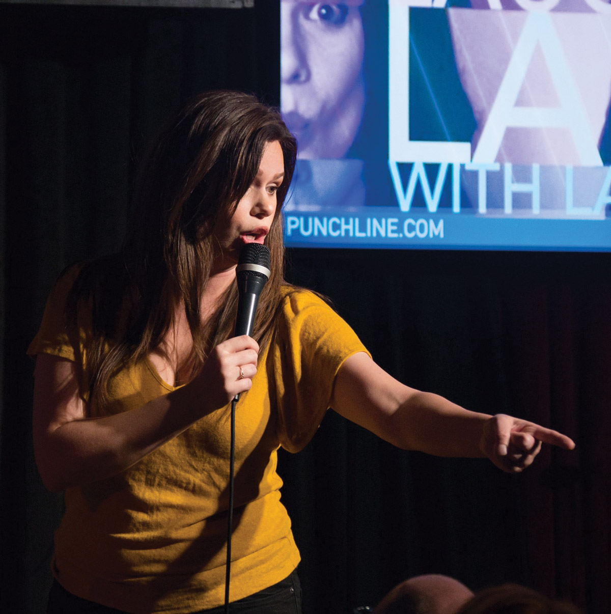 Lace Larrabee pointing at someone in a crowd during her standup performance
