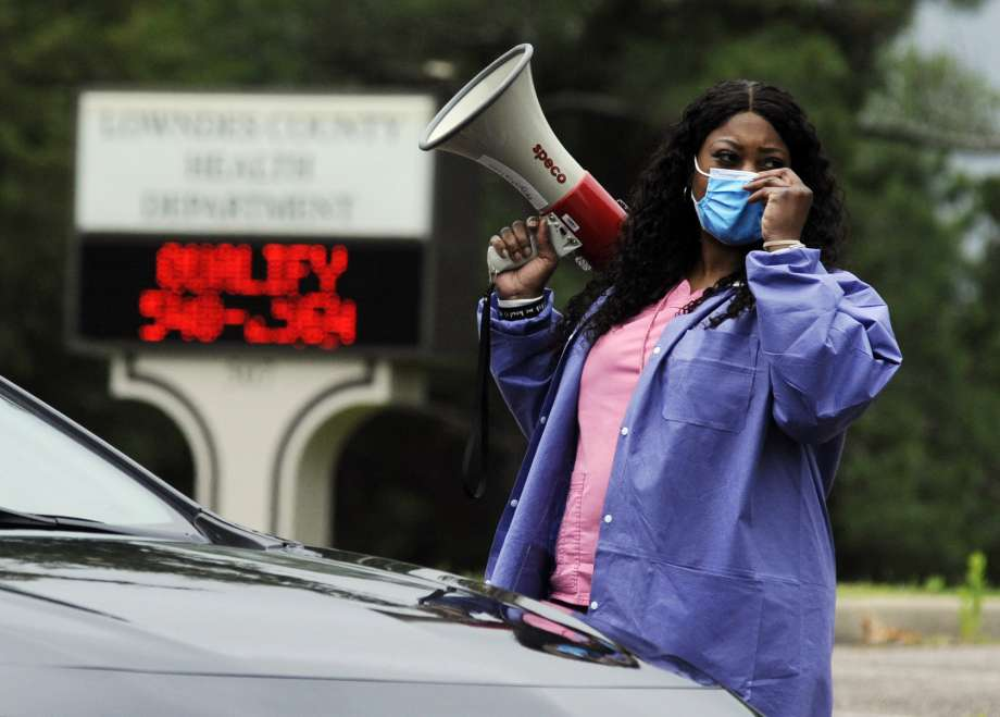 """In this May 27, 2020, photo, health care worker Tonya Wilkes adjusts her mask while working at a Lowndes County coronavirus testing site in Hayneville, Ala. Experts say Lowndes County and nearby poor, mostly black counties in rural Alabama are now facing a """"perfect storm"""" as infections tick up: a lack of access to medical care combined with poverty and the attendant health problems that can worsen the outcomes for those who become sick. Photo: Jay Reeves, AP / Copyright 2020 The Associated Press. All rights reserved."""