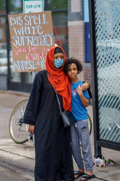 A Somali American mother and her child stand during a protest in Minneapolis against the death of Ge...