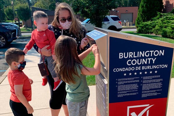 Nicole Flaherty's 7-year-old daughter helped insert a ballot in a drop box ahead of Election Day in New Jersey. Ballots can also be mailed or delivered in person.
