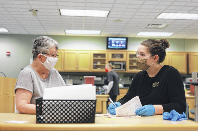 Student Nicole Caser (right) speaks with Carol Carpenter, of Cincinnati, before her vaccine during the clinic held at Ohio Northern University in Ada.