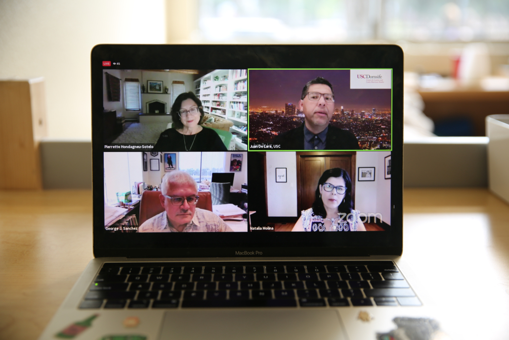 Photo of a MacBook Pro showing four Zoom screens that each include a person with separate backgrounds. The background of the laptop is blurred.